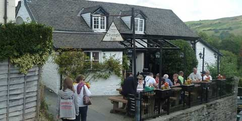 Guests enjoying lunch outside the Triangle Inn with pretty views of the surrounding countryside